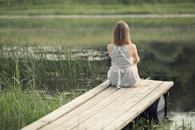 Meisje zit op de pier bij het meer en droomt van het leven