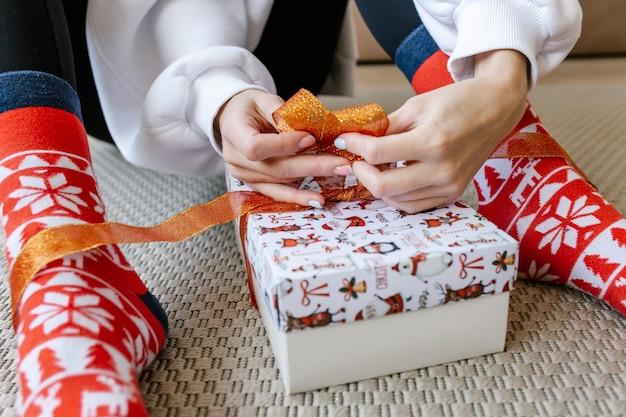 Meisje zit op de vloer en knoopt een lint vast terwijl ze een geschenk inpakt. handen bindend lint op geschenkdoos. kerstvoorbereidingen en cadeauverpakking.