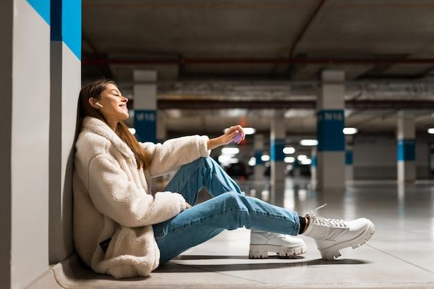 Meisje zit op de vloer van een ondergrondse parkeergarage