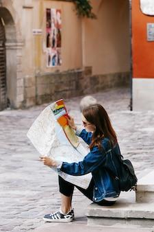 Meisje zit op de voetstappen kijkt naar de toeristische kaart