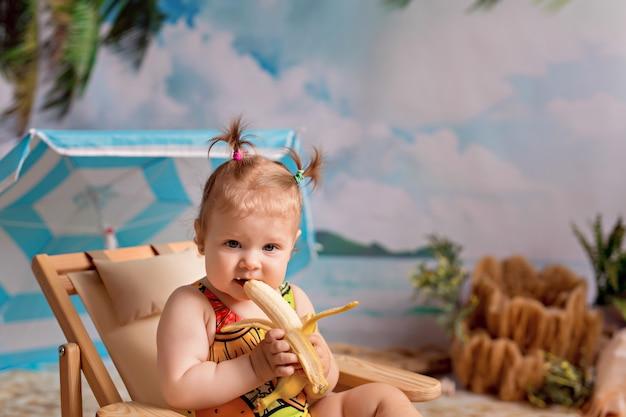 Meisje zit op een ligstoel, zonnebaadt op zandstrand met palmbomen aan zee en eet een banaan