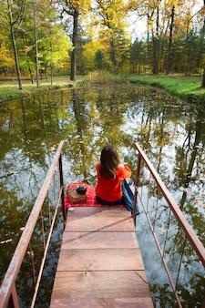 Meisje zit op houten brug door meer
