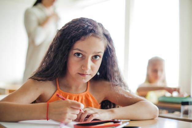 Meisje zitten aan de balie met een potlood