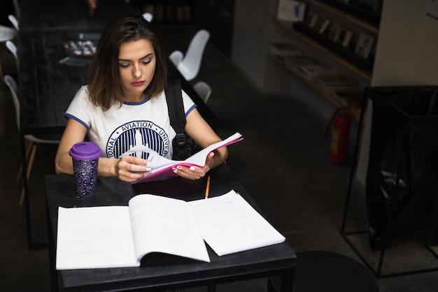 Meisje zitten aan tafel lezen bladzijde