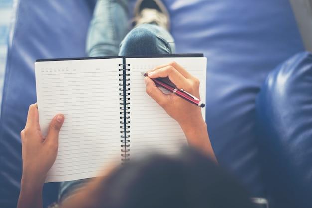 Meisje zitten in een coach schriftelijke instructies op notebook