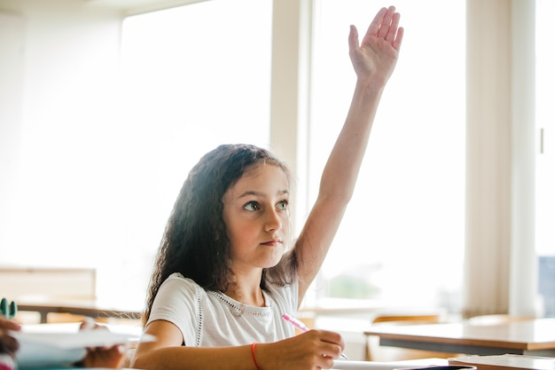 Meisje zitten op school tafel verhogen hand