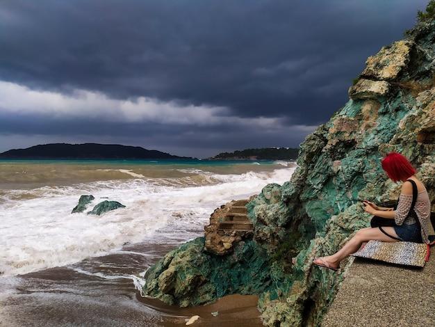 Meisje, zittend aan zee op de rotsen bij bewolkt weer