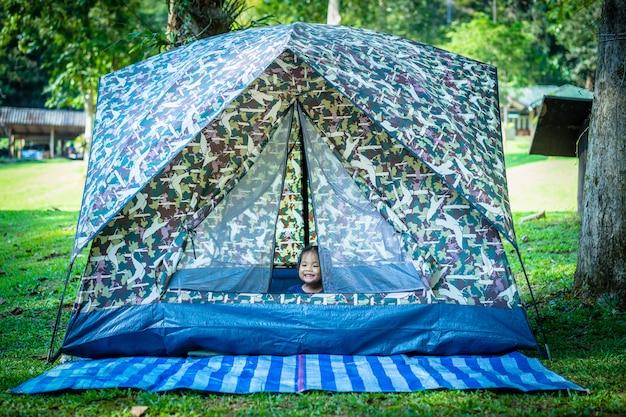 Meisje, zittend in de tent tijdens het kamperen.