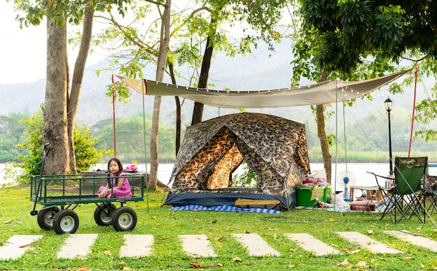 Meisje, zittend in de wagen tijdens het kamperen.