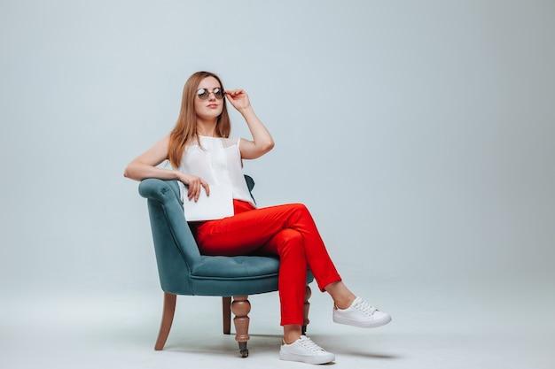 Meisje zittend in een stoel met een boek en een bril