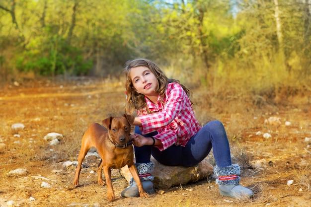 Meisje, zittend in het dennenbos kleine hond te houden