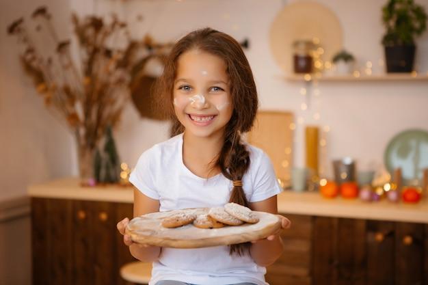 Meisje, zittend in kerstkeuken op tafel