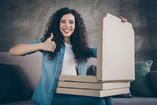 Meisje zittend op de bank bedrijf in handen taart dozen met thumbup advies op moderne loft industriële stijl interieur kamer