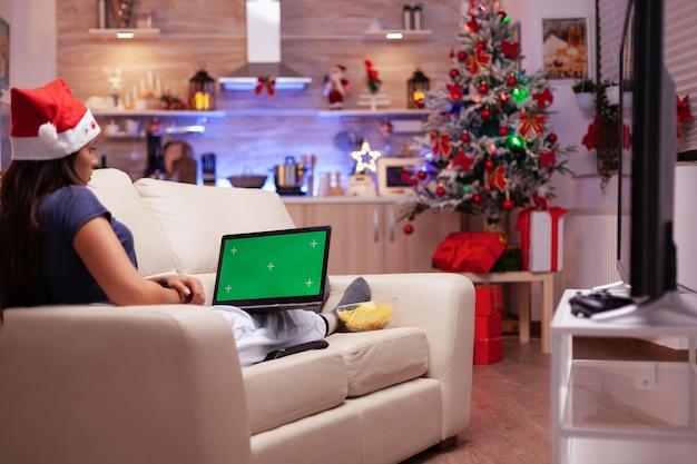 Meisje zittend op de bank met mock-up groen scherm chroma key laptop