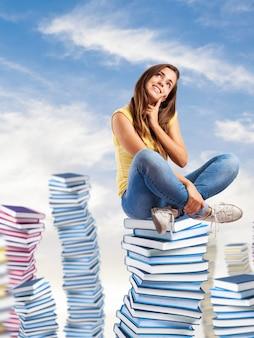 Meisje zittend op de bergen van boeken en glimlachen