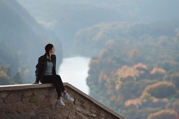 Meisje, zittend op de heuvel en kijkt in de verte van het bos en de rivier