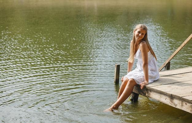 Meisje zittend op de pier en kijken naar de rivier.