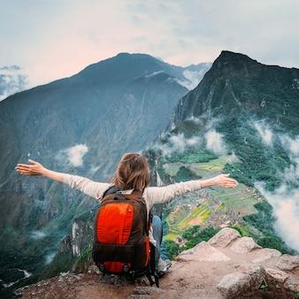 Meisje zittend op de rand van de rots en genieten van landschap van machu picchu