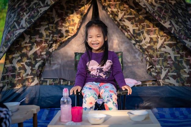 Meisje, zittend op de stoel tijdens het kamperen.