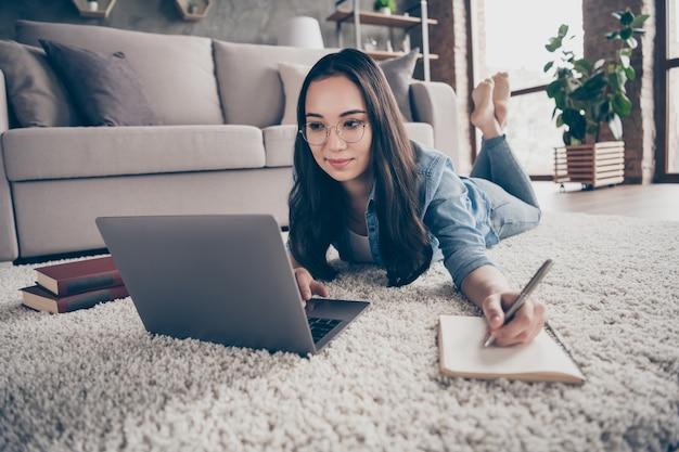 Meisje zittend op de vloer en werkt op laptop