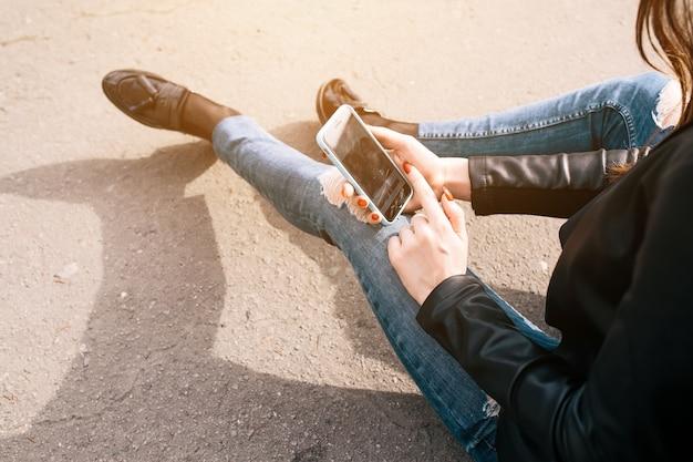 Meisje zittend op de vloer met behulp van haar smartphone
