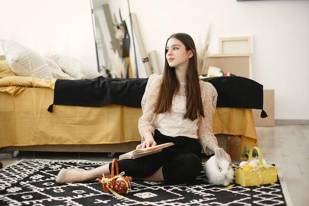 Meisje zittend op de vloer met een boek omringd door pasen-thema's.