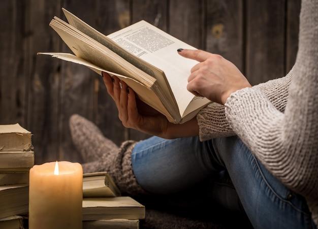 Meisje zittend op de vloer omringd door veel witte boeken en een grote kaars