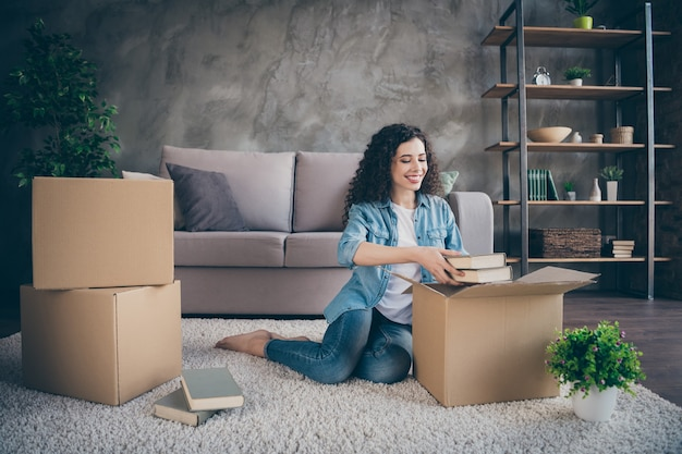 Meisje zittend op de vloer tapijt openen uitpakken haar eigen spullen uitpakken in moderne loft industriële stijl interieur woonkamer