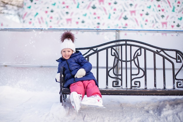 Meisje, zittend op een bankje in de ijsbaan