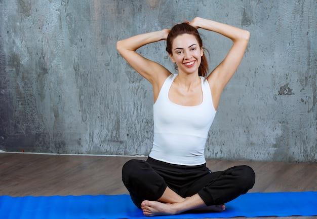 Meisje zittend op een blauwe yoga mat in lotushouding en mediteren.