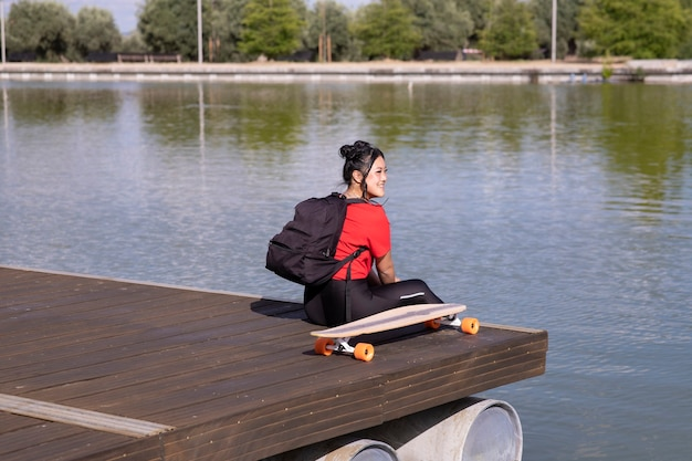 Meisje, zittend op een dok bij een meer, met rugzak