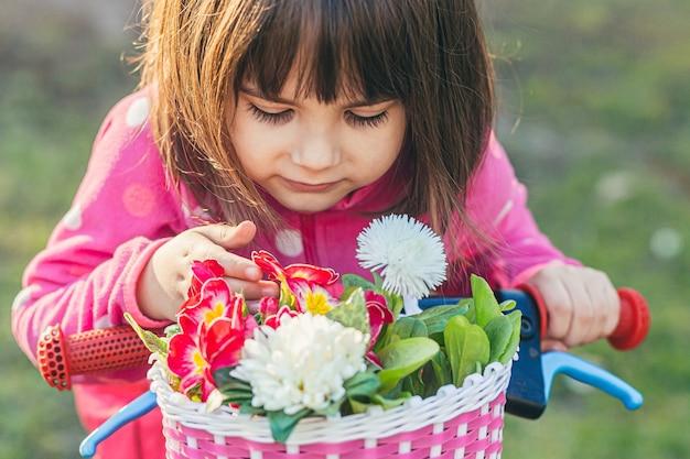 Meisje zittend op een fiets voorovergebogen en bloemen snuivend