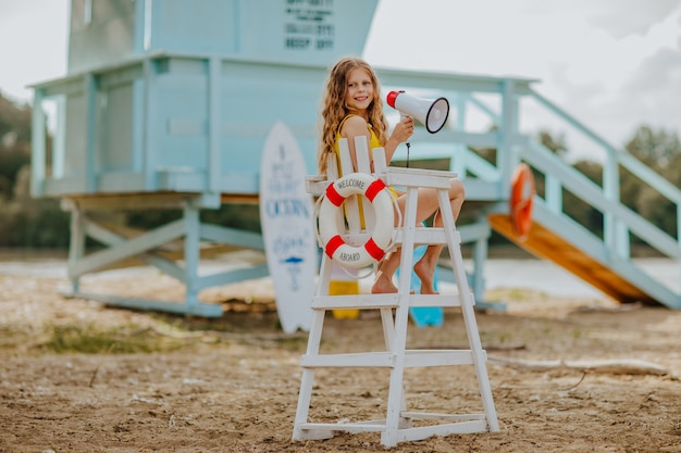 Meisje zittend op een hoge stoel met levenslijn en poseren met megafoon