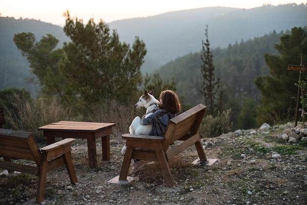 Meisje zittend op een houten bankje met een witte hond omgeven door groen en heuvels onder zonlicht