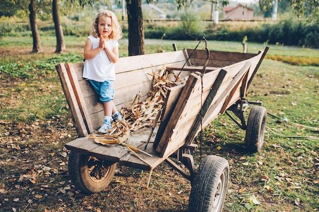Meisje zittend op een oude houten wagen in het dorp