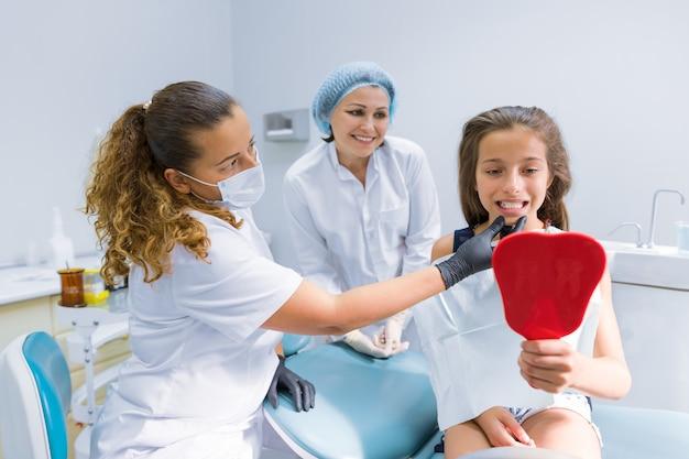 Meisje, zittend op een stoel bij de tandarts