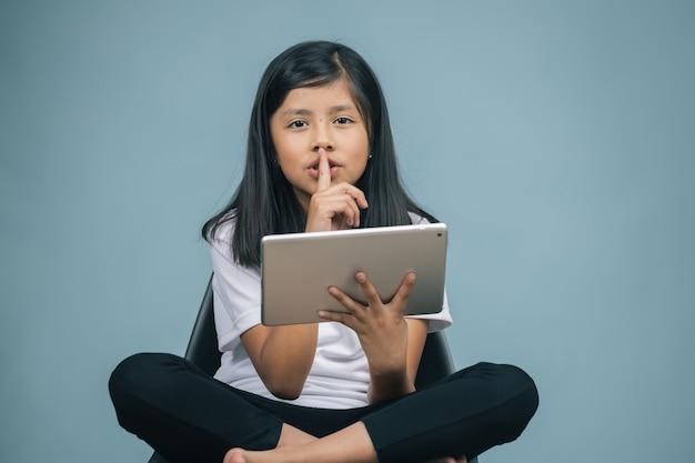 Meisje, zittend op een stoel kijken naar tablet