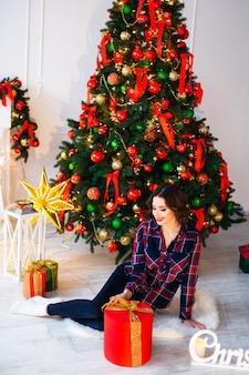 Meisje zittend op een vloer in de buurt van een kerstboom en een geweldig cadeau en kijk naar de zijkant