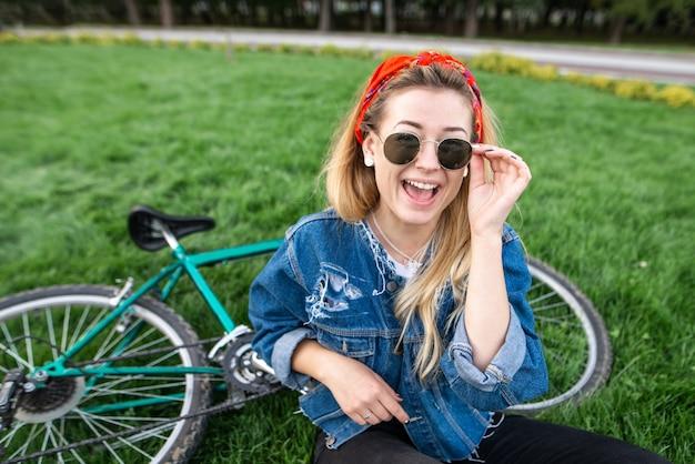Meisje zittend op groen gras in een park in de buurt van een fiets
