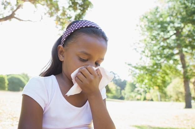 Meisje, zittend op het gras blaast haar neus