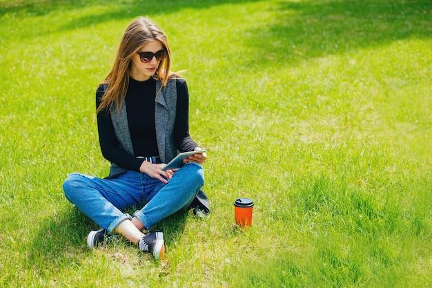 Meisje zittend op het gras met koffie en tablet op straat.