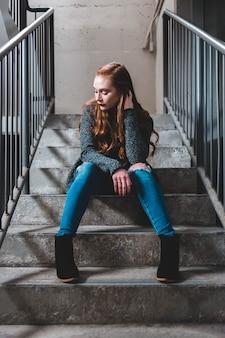 Meisje, zittend op trappen
