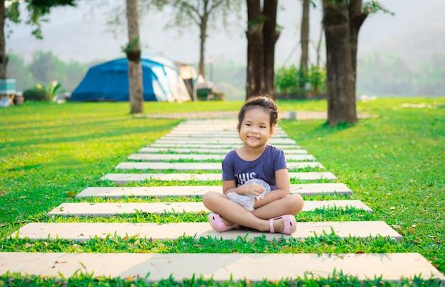 Meisje, zittend op voetpad tijdens het kamperen