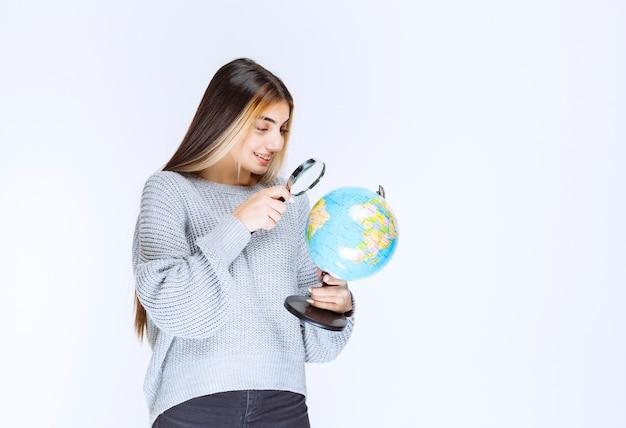 Meisje zoekt locaties over de hele wereld met een vergrootglas.