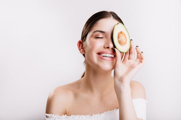Meisje zonder make-up houdt een halve avocado vast en bedekt een deel van het gezicht. vrij vrouwelijk model met donker haar leidt een gezonde levensstijl.