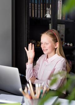 Meisje zwaaien naar haar collega's via haar webcamera
