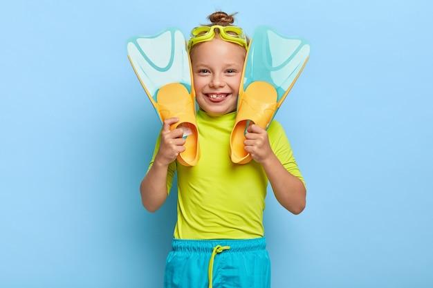 Meisje zwemmer draagt een bril, houdt flippers vast