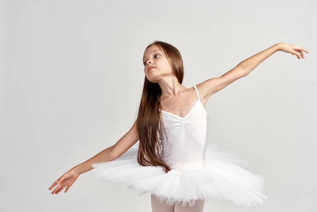 Meisjeballerina in een wit kostuum in pointeschoenen
