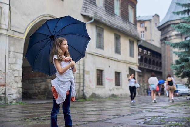 Meisjekind in de regen met een paraplu, achtergrond van de toeristen de oude stad