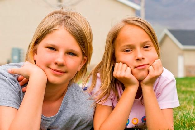 Meisjes (8-11) die op gras met huis op achtergrond, portret liggen